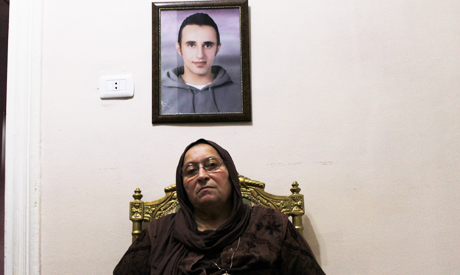 Laila Marzouk sits behind the iconic portrait of her son Khaled Said on the third anniversary of his death (Photo: Diaa Galal)